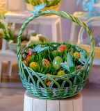Wooden Easter eggs in a green basket on a stub. Wood decorated Easter eggs in a green basket on a wooden stub with bright colorful defocused background Stock Images