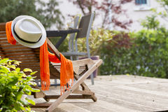 Wooden easy chair on a garden lawn, hat with flower. Lounge chair on wooden terrace garden. Paris Stock Photo