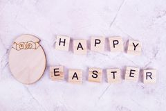 Wooden egg and inscription. Happy Easter card and egg. Beige card for Easter royalty free stock photo