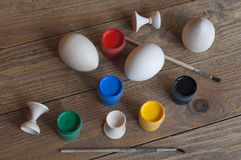 Wooden eggs, paints and paintbrushes. Wooden eggs, paints and paintbrushes on a wooden table. Decoration for Happy Easter Royalty Free Stock Image