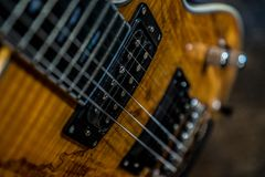 Wooden electric guitar. Close up artistic angle on wooden electric guitar neck and strings royalty free stock image