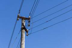 Wooden electric pole with wires in the blue sky in the background Stock Photo