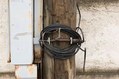 Wooden electric pole with wires and grey metal junction box. Electricity power supply chain. Town`s energy Royalty Free Stock Photo