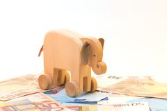 Wooden elephant with money Royalty Free Stock Images