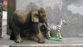 Wooden elephant and plaster zebra doll Stock Photography