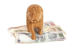 Wooden elephant sculpture on Indian  Rupee banknotes Stock Images