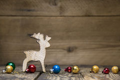 Wooden elk or reindeer on rustic country style background. Wooden elk or reindeer on old rustic country style background with old christmas balls for a natural Stock Image