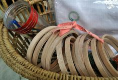 Wooden embroidery hoops and needle work accessories in basket Stock Images