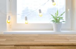 Wooden empty board in front of blurred holiday window background Royalty Free Stock Image