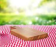 Wooden empty board over picnic cloth on a grass. Wooden board on picnic cloth outdoors.Food advertisement design.Empty wooden deck Royalty Free Stock Photos