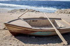 Wooden empty boat with two oars on beach. Photo of the Wooden boat with two oars on beach Royalty Free Stock Images