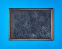 Wooden empty chalk board on a blue background. Copy space royalty free stock images