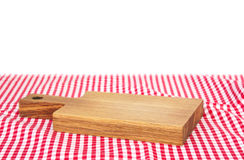 Wooden empty cutting board over picnic tablecloth. Wooden board over red checked picnic cloth isolated.Food advertisement design element.Restaurant concept Royalty Free Stock Image