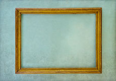 Wooden empty frame hanging on a green wall Royalty Free Stock Image