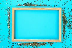 A wooden empty frame on a pastel background surrounded by shiny decorative stars and balls. A wooden empty frame on a pastel background surrounded by shiny Royalty Free Stock Image