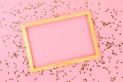 A wooden empty frame on a pastel background surrounded by shiny decorative stars and balls. stock photos