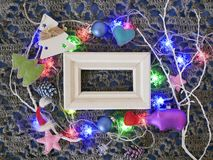 Wooden empty frame on a textural knitted background decorated with lighted illumination. Christmas decor, felt hearts, the concept of congratulations on winter royalty free stock images