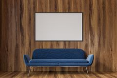 Empty wooden room, blue sofa, poster. Wooden empty room interior with a dark blue sofa standing on a woden floor. A poster. 3d rendering, mock up Stock Image