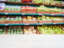 Wooden empty table in front of blurred supermarket vegetables shelf Stock Image