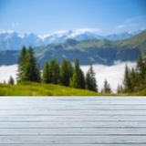 Wooden emty board or table and austrian alps in the background.  stock photo