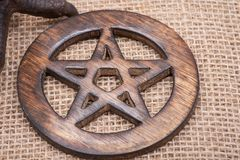 Wooden encircled pentagram symbol on burlap. Five elements. Wooden encircled pentagram symbol on burlap background. Five elements: Earth, Water, Air, Fire royalty free stock photography