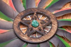 Wooden encircled Pentagram symbol with Green Aventurine in the middle of a circle made of colorful parrot feathers. Five elements. Earth, Water, Air, Fire stock photos