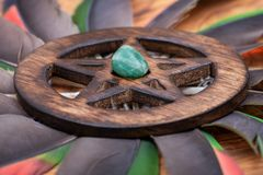 Wooden encircled Pentagram symbol with Green Aventurine in the middle of a circle made of colorful parrot feathers. Five elements. Earth, Water, Air, Fire stock photography