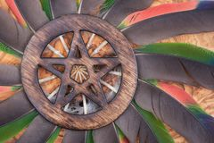 Wooden encircled Pentagram symbol in the middle of a circle made of colorful parrot feathers. Five elements. Earth, Water, Air, Fire, Spirit royalty free stock images