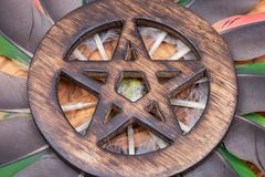 Wooden encircled Pentagram symbol with Unakite stone in the middle of a circle made of colorful parrot feathers. Five elements. Earth, Water, Air, Fire, Spirit royalty free stock photos