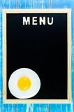 Wooden english alphabet menu and Fried egg on the blackboard. Stock Photo