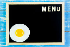Wooden english alphabet menu and Fried egg on the blackboard. Wooden english alphabet menu and Fried egg on the blackboard Royalty Free Stock Photography