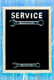 Wooden english alphabet service and wrench on the blackboard. Royalty Free Stock Photo