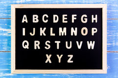 Wooden english alphabet A-Z on the blackboard. Wooden english alphabet A-Z on the blackboard Royalty Free Stock Photos