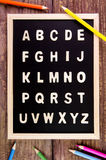 Wooden english alphabet A-Z on the blackboard.Color pencil on wo. Oden table Stock Photo