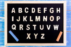 Wooden english alphabet A-Z on the blackboard.on wooden table. Wooden english alphabet A-Z on the blackboard.on wooden table Royalty Free Stock Images
