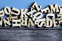 Wooden English letters in bulk and on wooden blue background. Education royalty free stock photo