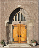 Wooden entrance door of church. Wooden entrance door with decorative fittings in arch shaped wall recess of the Catholic Church at Hoogmade, the Netherlands on Stock Photo