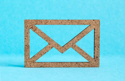 Wooden envelope icon on blue background Stock Photo