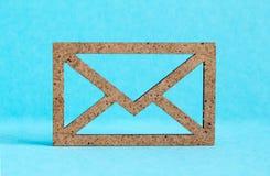 Wooden envelope icon on blue background.  Stock Photo