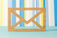 Wooden envelope icon on blue striped background.  Royalty Free Stock Photo