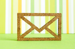 Wooden envelope icon on green striped background.  Royalty Free Stock Photography