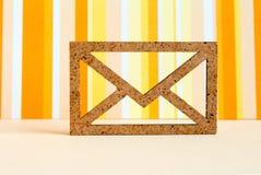 Wooden envelope icon on orange striped background.  Royalty Free Stock Images