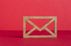 Wooden envelope icon on red background.  Stock Photo
