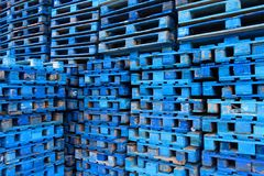 Pile of wooden euro pallets painted in blue. Wooden euro pallets painted in blue stacked on the ramp of a transport company Stock Images