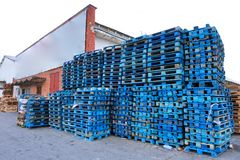 Pile of wooden euro pallets painted in blue. Wooden euro pallets painted in blue stacked on the ramp of a transport company Royalty Free Stock Images