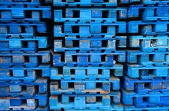 Pile of wooden euro pallets painted in blue. Wooden euro pallets painted in blue stacked on the ramp of a transport company Royalty Free Stock Image