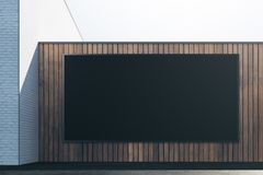 Wooden exterior with signboard front. Front view of abstract brick wooden exterior with empty black signboard. Advert, commerce, retail and signboard concept Stock Image