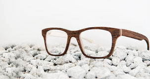 Wooden eyeglasses on stones. Stones under the sun texture yellow Royalty Free Stock Images