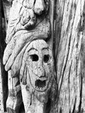 Wooden Face Carving in Tree. Wooden carving of a face in Caribbean tree bark by local artist. Mayan influenced carving of scary expression stock photo