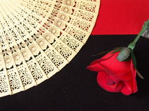 Wooden fan. Carved wooden japanese fan with a red rose on red and black velvet cloth Stock Photo